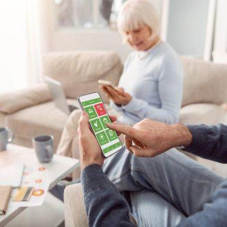 Älteres Ehepaar sitzend im Wohnzimmer beide lächelnd mit Blick auf das Smartphone